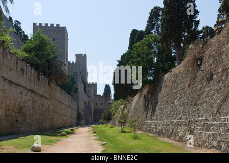 Medieval moat round the walls of the Old Town with the Palace of the Grand Masters to the left, Rhodes Town, Rhodes, - Stock Photo