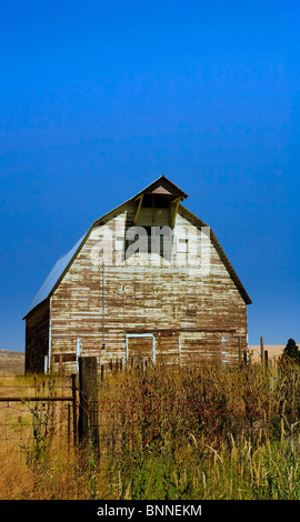 Old barn with barb wire fence in front under blue sky - Stock Photo