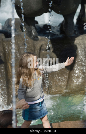 Little girl playing close to city fountain - Stock Photo