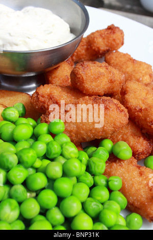 Plate of scampi with tartar sauce, chips and peas - Stock Photo