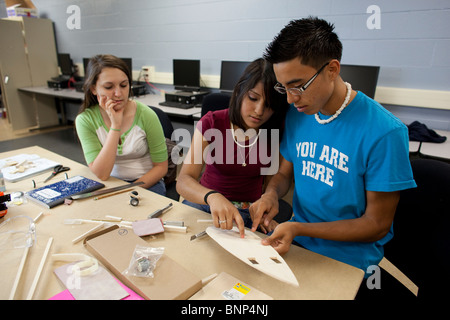 Male and female students work as a team to design and build a model solar car in engineering class at Manor New - Stock Photo