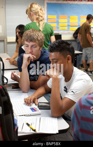 Hispanic, Anglo boys work on computer together doing research for class project at Manor New Tech High School in - Stock Photo
