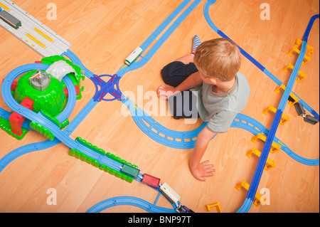 A MODEL RELEASED six year old boy playing with a TOMY Thomas the tank engine train set in the Uk - Stock Photo