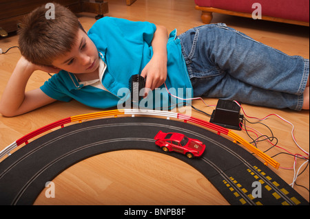 A MODEL RELEASED ten year old boy playing with a Hornby Scalextric racing car set game in the Uk - Stock Photo