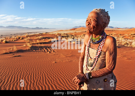 Elderly Bushman / San woman standing in desert - Stock Photo