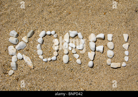 KORFU spelled out in pebbles on a beach at Kassiopi on the Greek Mediterranean island of Corfu Greece GR - Stock Photo