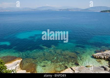 Rocky coastline at Kassiopi on the Greek Mediterranean island of Corfu Greece GR with Albanian mountains on horizon - Stock Photo
