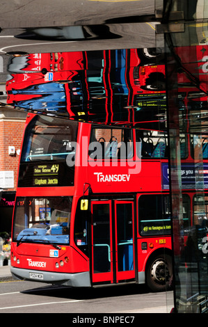Red London bus with reflections in shop, King's Road, Chelsea, London, England, UK - Stock Photo