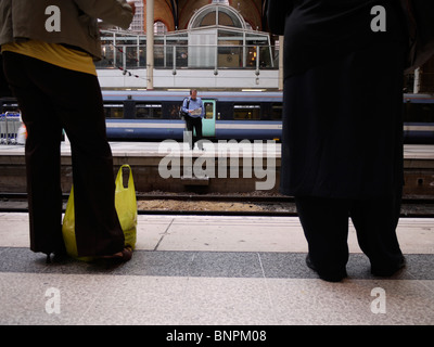 rail passengers waiting on platform at liverpool street station - Stock Photo