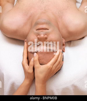 Man getting a relaxing massage in spa salon - Stock Photo