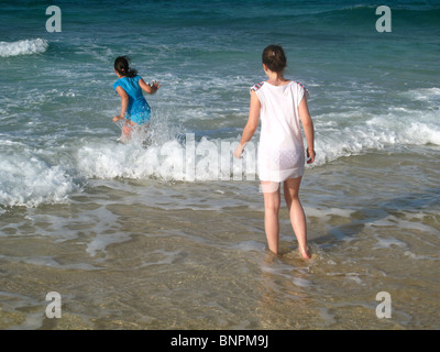 Two girls playing in waves on beach - Stock Photo