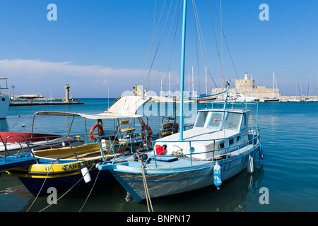 Boats in front of the old Agios Nikolaos fortress and lighthouse in Mandraki Harbour, Rhodes Town, Rhodes, Greece - Stock Photo