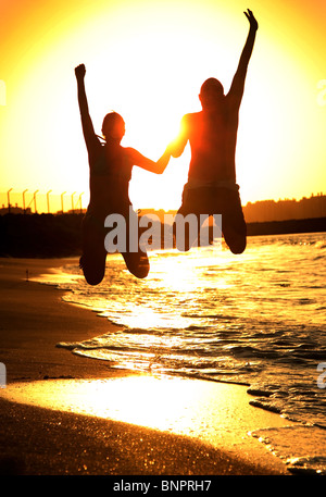 Two happy jumpers on the beach at sunset - Stock Photo