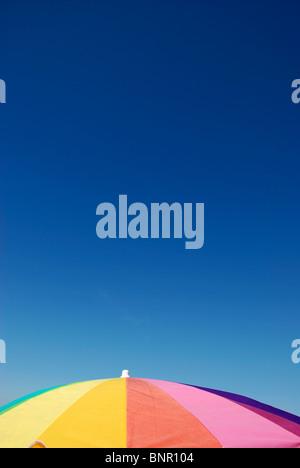 Rainbow colored sun umbrella at the beach against clear blue sky. - Stock Photo