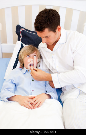 Worried father checking his son's temperature - Stock Photo