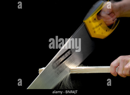 An 'action' image of a man using a hand saw to cut a piece of wood. The saw has the makers name, 'Stanley',written - Stock Photo
