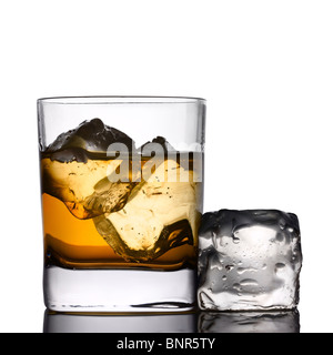Glass of whiskey on the rocks with ice-cube (isolated against white) - Stock Photo