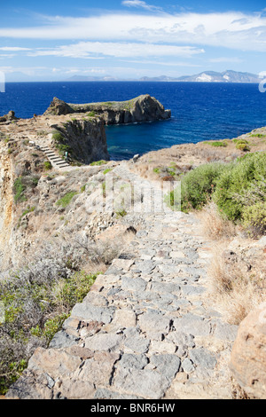 Path to the headland on the island Panarea of Aeolian Islands. Island Lipari and Vulcano in the distance. - Stock Photo