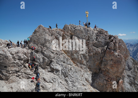 Tourists climbing to the Golden Cross - the highest point in Germany on the summit of Zugspitze at 2,962m above - Stock Photo