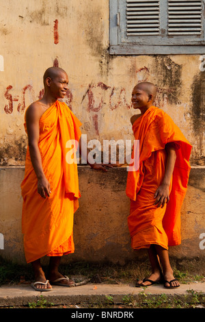 Cambodian novice monks chatting outside a colonial building - Kandal Province, Cambodia - Stock Photo