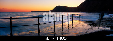 High tide causing waves to sweep over the jetty at Sidmouth, Devon. Taken at sunset - Stock Photo