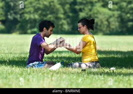 Young couple sitting on the grass tying a bracelet on each other's wrist - Stock Photo