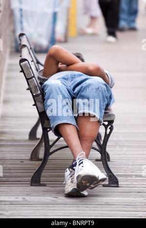 A man lying on his back, asleep on a public bench on Brooklyn bridge, Manhattan, New York, USA - Stock Photo