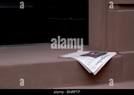 a newspaper delivered and lying on a doorstep outside a city house in Greenwich Village, Manhattan, New York, USA - Stock Photo