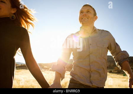Couple run while holding hands and smiling in an open field. - Stock Photo