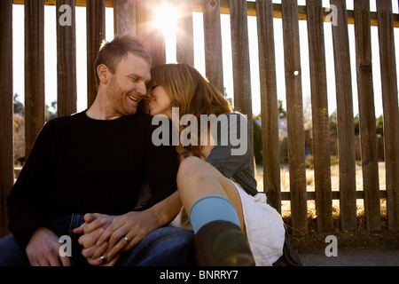 Couple sits against a fence. - Stock Photo