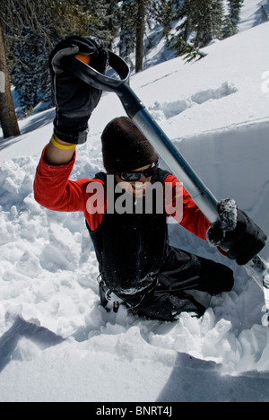 A young man digs an avalanche pit to examine the snow pack and determine the avalanche danger, in the Lake Tahoe - Stock Photo