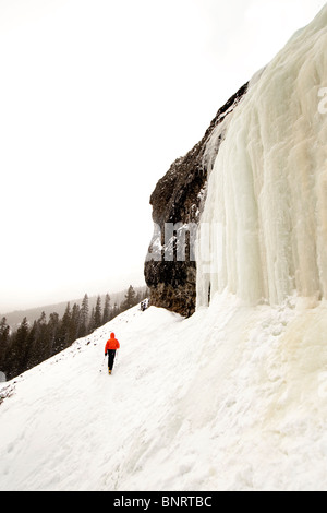 Man hiking in the snow near a frozen waterfall. - Stock Photo