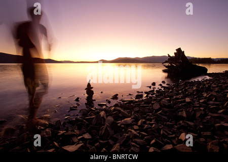 A male figure watching sunset over a lake and mountains in Idaho. - Stock Photo