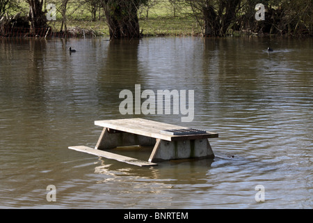 Wooden picnic table in a flooded river Wolvercote, Oxfordshire