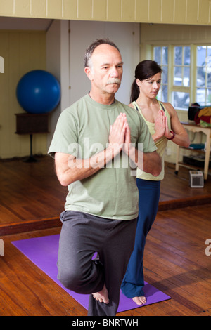 An older man in front of a younger woman practices a yoga position in a small studio. - Stock Photo