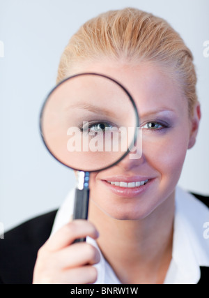Smiling woman looking into a magniying glass - Stock Photo