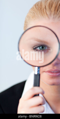 Serious Business woman looking through a magnifying Glass - Stock Photo