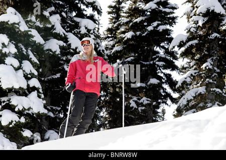 A woman skis among snow flocked trees. - Stock Photo