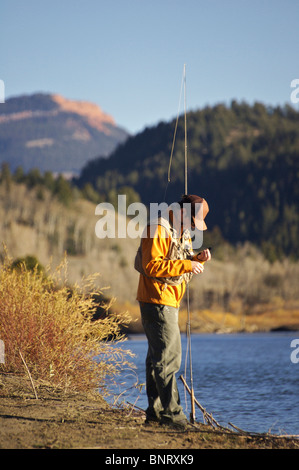 A man prepares a fly on the Gros Ventre River in Wyoming. - Stock Photo