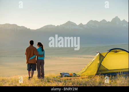 A young couple enjoy the last rays of the day while camping. - Stock Photo