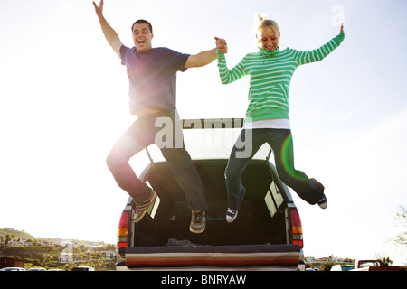 Couple jump from a truck in a parking lot. - Stock Photo
