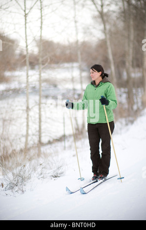 Woman cross country skiing next to river. - Stock Photo