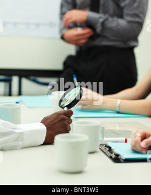 Businessman holding a magnifying glass - Stock Photo