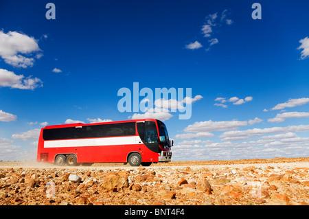 A bus drives along a dirt road in outback Queensland, near Birdsville, Queensland, AUSTRALIA. - Stock Photo