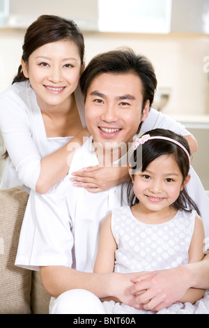 Portrait of a young family at home - Stock Photo