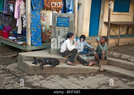 Three children playing cards in the street in Andasibe Village in western Madagascar. A dog is sleeping on the step - Stock Photo
