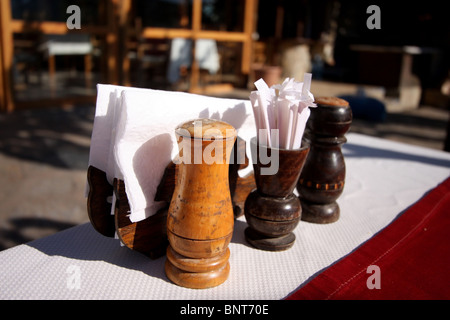 Restaurant outside tables, close up on the wooden salt and pepper pots, napkins, and tooth picks - Stock Photo