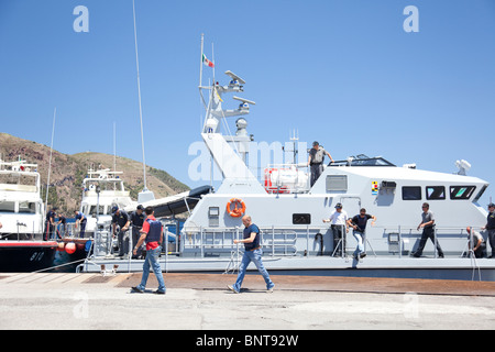 Italian police force Guardia di Finanza having an operation with some vessels and policemen in the port. - Stock Photo