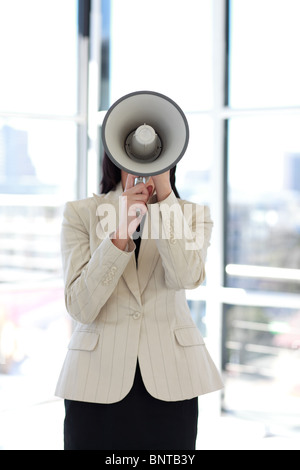 Businesswoman shouting through megaphone - Stock Photo