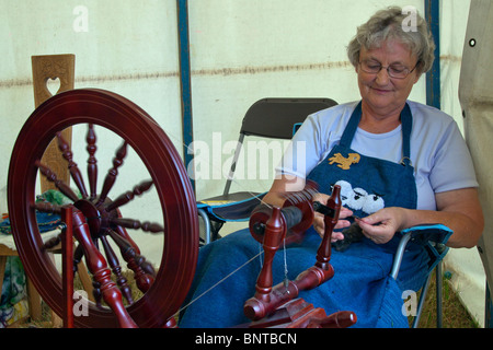 Old dear using an ancient spinning wheel, showing the art of wool spinning - Stock Photo